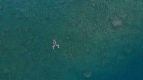 ANTENA: a mulher que flutua na superfície da água azul, nadando no mar Mediterrâneo transparente, parte superior vê para baixo, c Imagem de Stock Royalty Free