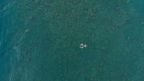 ANTENA: a mulher que flutua na superfície da água azul, nadando no mar Mediterrâneo transparente, parte superior vê para baixo, c Imagens de Stock Royalty Free