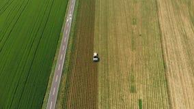 Antena: o trator que trabalha na terra cultivada dos campos, ocupação da agricultura, opinião da parte superior para baixo do cer video estoque