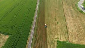 Antena: o trator que trabalha na terra cultivada dos campos, ocupação da agricultura, opinião da parte superior para baixo do cer filme
