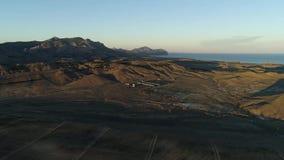 Antena para el paisaje hermoso del campo verde en puesta del sol en fondo del mar azul y del cielo nublado tiro Valle de oro y metrajes