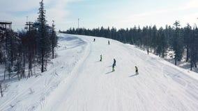 Antena para a inclinação nevado com um esqui do grupo de pessoas e uma snowboarding em um dia ensolarado, conceito perigoso do es filme