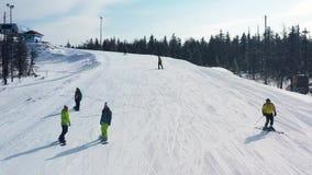 Antena para a inclina??o nevado com um esqui do grupo de pessoas e uma snowboarding em um dia ensolarado, conceito perigoso do es filme
