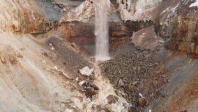 Antena para la mina rocosa con la corriente sucia del agua que cae abajo y vieja basura en el ambiente de tierra, contaminado almacen de metraje de vídeo
