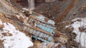 Antena para la mina rocosa con la corriente sucia del agua que cae abajo y vieja basura en el ambiente de tierra, contaminado metrajes