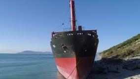 Antena para o barco do reboque amarrado na costa do oceano perto do monte com as árvores verdes no fundo do céu azul tiro Vermelh vídeos de arquivo