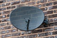 Antena parabólica de la TV en una pared de ladrillo foto de archivo libre de regalías