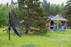 Antena parabólica delante de una casa o de una cabaña abandonada Foto de archivo libre de regalías