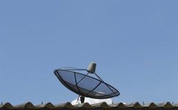 Antena parabólica en el tejado con el cielo azul imagen de archivo libre de regalías