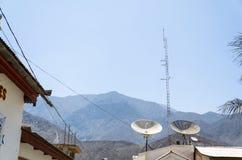 Antena parabólica en el tejado de la casa con la torre de radio en el cielo azul de la nube del día soleado imágenes de archivo libres de regalías