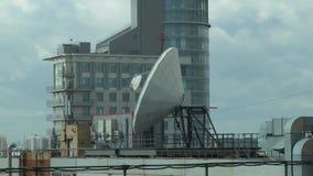 Antena parabólica en el tejado en el fondo del edificio almacen de metraje de vídeo