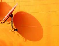 Antena parabólica en la pared anaranjada Imagenes de archivo