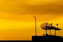 Antena parabólica en la puesta del sol imagen de archivo