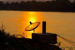 Antena parabólica en la reflexión en el río en backgrou de la puesta del sol Imagenes de archivo