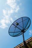 Antena parabólica negra de la comunicación de la antena sobre el cielo azul soleado Fotografía de archivo