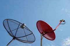 Antena parabólica preta e vermelha com o céu azul imagem de stock