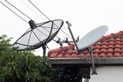 Antena parabólica preto e branco e antena da tevê na vila velha, receptor digital parabólico para dados de uma comunicação no roo imagens de stock