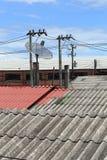 Antena parabólica y antenas de TV en el tejado de la casa Imagen de archivo libre de regalías