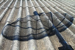 Antena parabólica de la sombra en el tejado Fotografía de archivo