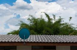 Antena parabólica verde en el tejado con un cielo azul hermoso Fotos de archivo libres de regalías