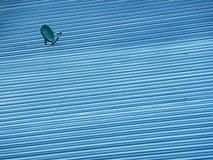 Antena parabólica verde pequena no telhado azul da folha de metal Imagem de Stock
