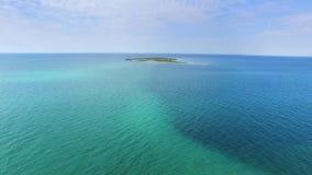 ANTENA: Pequeña isla en aguas poco profundas del mar azul almacen de video