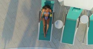 Antena: Piękna dziewczyna kłama na lounger basenem i pić koktajl zbiory