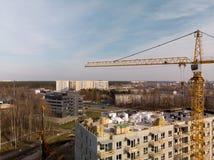 Antena plac budowy z wielkim operacyjnym jaskrawym żółtym żurawiem blisko domu obrazy royalty free