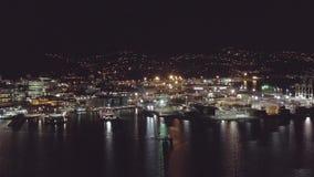 Antena, porto da noite e skyline da cidade com os barcos que viajam através da baía video estoque