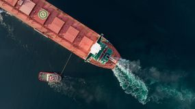 Antena strzał ładunku statek zbliża się port z pomocą holować statek obraz royalty free