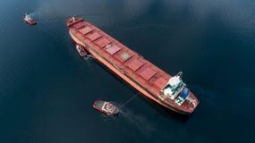 Antena strzał ładunku statek zbliża się port z pomocą holować statek obrazy royalty free