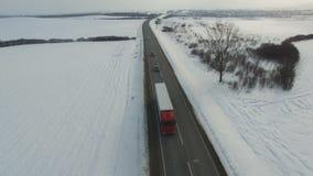 Antena strzał ciężarówka i samochodu jeżdżenia zimy droga w śnieżnym polu zbiory wideo
