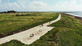 Antena strzelał dwa cyklisty jedzie wzdłuż seashore linii brzegowej i pedestrians chodzić Paphos Cypr Rowerzysta rekreacyjna prze zbiory