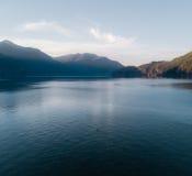 Antena strzelał kayaker na jeziorze z górami podczas gdy zmierzch zdjęcia stock