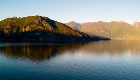 Antena strzelał kayaker na jeziorze z górami podczas gdy zmierzch Fotografia Stock