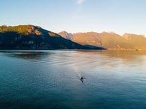 Antena strzelał kayaker na jeziorze z górami podczas gdy zmierzch Obraz Royalty Free