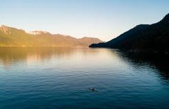 Antena strzelał kayaker na jeziorze z górami podczas gdy zmierzch Obrazy Royalty Free