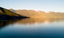 Antena strzelał kayaker na jeziorze z górami podczas gdy zmierzch Zdjęcie Stock
