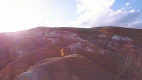 Antena: Una chica joven que se coloca en la montaña roja que vuela su cometa en altas montañas en fondo la idea de la libertad, metrajes
