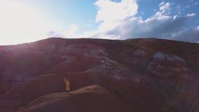 Antena: Una chica joven que se coloca en la montaña roja que vuela su cometa en altas montañas en fondo la idea de la libertad, almacen de video
