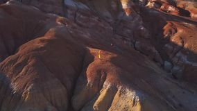 Antena: Una chica joven que se coloca en la montaña roja que vuela su cometa en altas montañas en fondo la idea de la libertad, almacen de metraje de vídeo