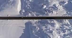 Antena vertical de arriba sobre el camino nevoso con los coches Puesta del sol o salida del sol soleada Montañas italianas de las almacen de video
