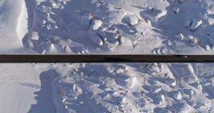 Antena vertical de arriba sobre el camino nevoso con los coches Puesta del sol o salida del sol soleada Montañas italianas de las metrajes