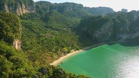 Antena: Vuelo sobre la montaña con una playa hermosa detrás de ella Playa de Railey, Krabi, Tailandia HD a cámara lenta almacen de video