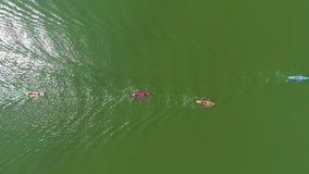 Antena wierzchołka puszek kolorowi kajaki z paddlers na rzeki nawierzchniowym odbija słońcu zbiory
