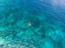 Antena wierzchołka puszka ludzie snorkeling na rafy koralowej tropikalnym morzu karaibskim, turkusowa błękitne wody Indonezja Wak zdjęcia stock