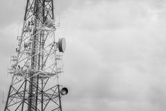 Antena y antena parabólica abstractas de la torre de la telecomunicación con fotografía de archivo