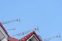 Antenas da telecomunicação no telhado de telha vermelha com o céu azul bonito Imagem de Stock Royalty Free