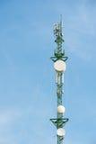 Antenas da tevê do mastro da telecomunicação com céu azul Fotografia de Stock Royalty Free