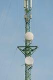 Antenas da tevê do mastro da telecomunicação com céu azul Fotografia de Stock